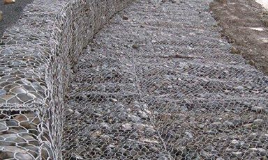 Maccaferri gabions are cages which are engineered from double twisted hexagonal woven steel wire mesh. Delivered flat-packed, our cages are assembled and then filled with stones at the project site - image courtesy of Maccaferri.